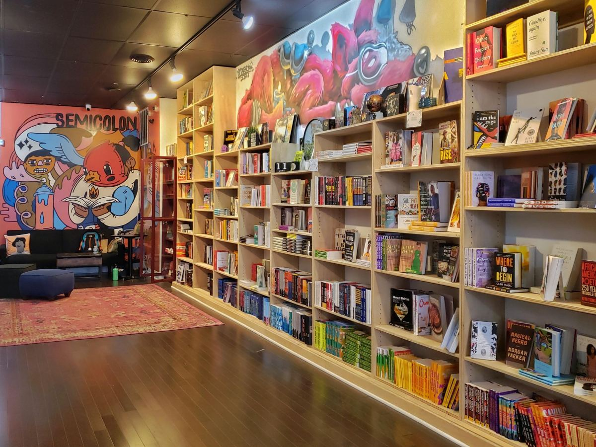 The inside of a bookstore, with the wall to the right covered in books and the far back wall featuring artwork.