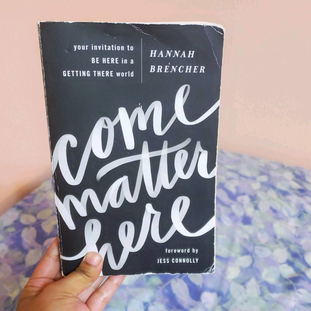 A brown hand holds up a worn copy of Come Matter Here by Hannah Brencher up against a background of a pink wall and a bed with a light blue and purple sheet over it.