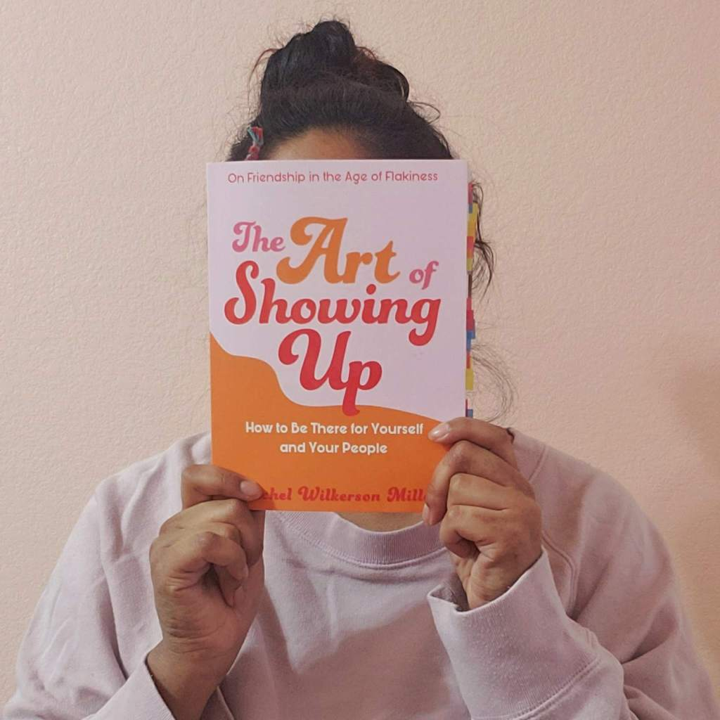 Brisa holds up a copy of the art of showing up by Rachel Wilkerson Miller, covering her face with it. She is in front of a pink wall and she is wearing a pink sweater.